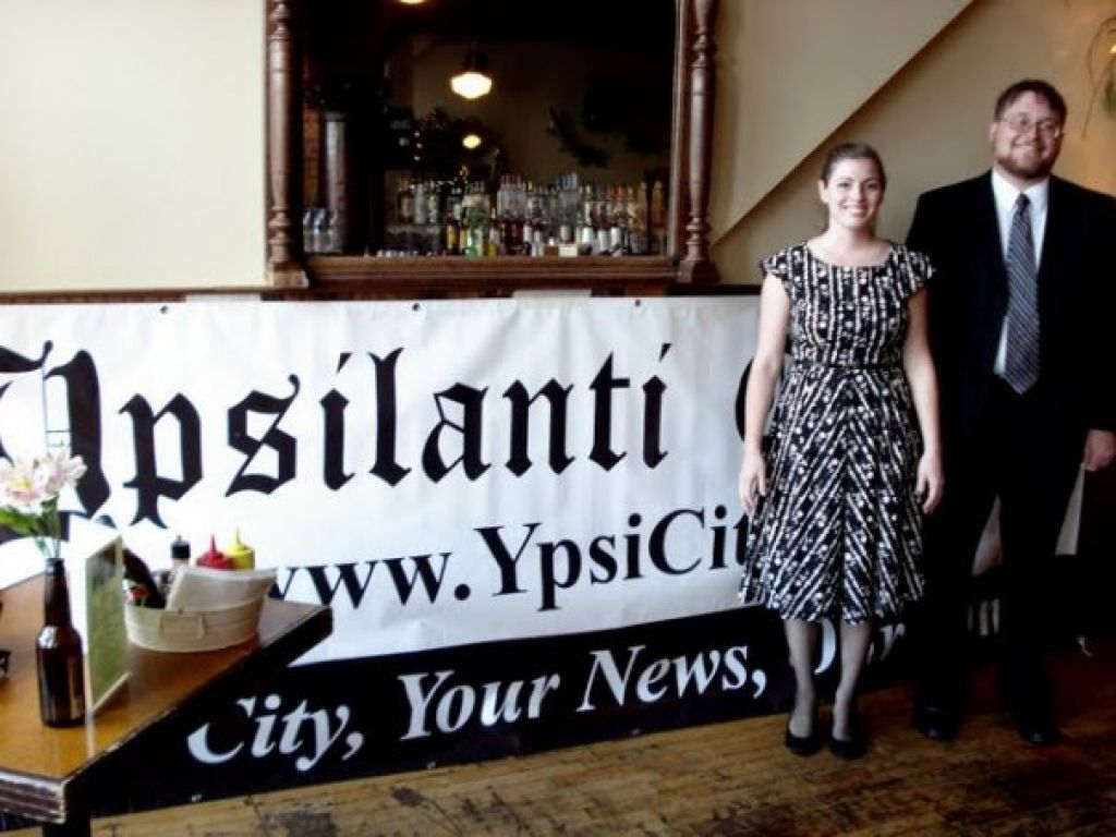 Christine Laughren and Dan DuChene, co-owners of the Ypsilanti Citizen, pose in front of their company's banner at Frenchie's during the Citizen's one-year anniversary party.