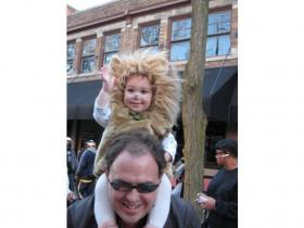 Nolan Wheeler, the 15-month-old lion who won the costume contest in his age group at last year's event, waves from above the shoulders of his father, Ken.