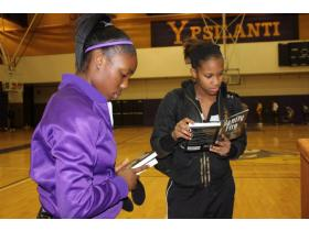 Carneysha McGee, left, and Cassandra Gibson, both Ypsilanti High School sophomores, select a few books during the Dec. 10 Book giveaway at Ypsilanti High School sponsored by the Michigan Education Association and the National Football League.