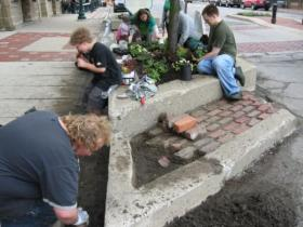 Volunteers and W.H. Canon employees plant flowers in Depot Town while Ypsilanti resident Mike Labadie repairs the planter's brick work on Ypsi PRIDE Day last year.
