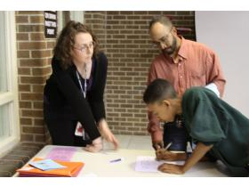 Autumn Fabricant, left, site coordinator for the Bright Futures program at Willow Run, helps eighth grade student, Ayleo Bowles, and his father, Jumaane Bowles, sign up for summer programming at the Freshman Flyer Academy informational dinner Thursday.