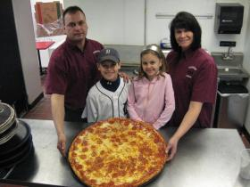 The Johnson family--Chuck, Nicholas, Keely and Dianne--stand with a 24-inch pepperoni pizza cooked Friday at their new Toarmina's store at 301 W. Cross Street.