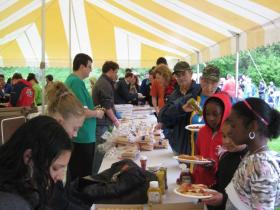Volunteers from the Ypsilanti area who participated in Ypsi PRIDE Day Saturday line up for a free lunch in Riverside Park provided by area restaurants and businesses.