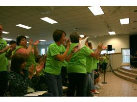 Lincoln paraprofessionals stand and cheer as Superintendent Lynn Cleary announces jobs will not be cut as planned.